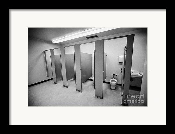Toilet Framed Print featuring the photograph cubicle toilet stalls in womens bathroom in a High school canada north america by Joe Fox