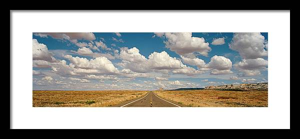 Scenics Framed Print featuring the photograph Desert Road With Cloud Formations Above by Gary Yeowell