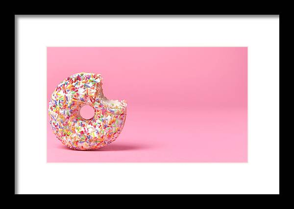 Unhealthy Eating Framed Print featuring the photograph Doughnut On Pink With Bite Out by Peter Dazeley