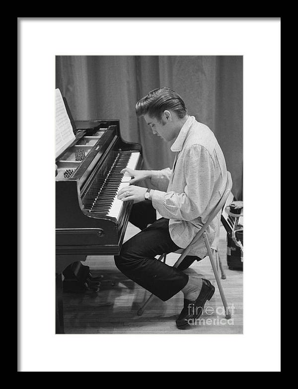Elvis Presley Framed Print featuring the photograph Elvis Presley on piano while waiting for a show to start 1956 by The Harrington Collection