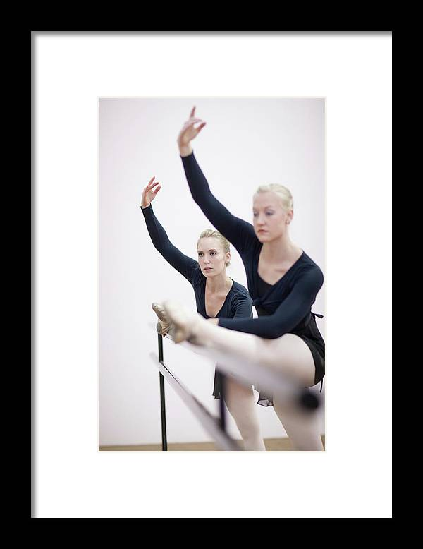 Ballet Dancer Framed Print featuring the photograph Female Ballerinas Stretching At The by Zero Creatives