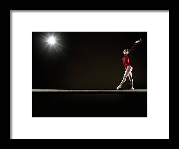 Human Arm Framed Print featuring the photograph Female Gymnast Balancing On Beam by Mike Harrington