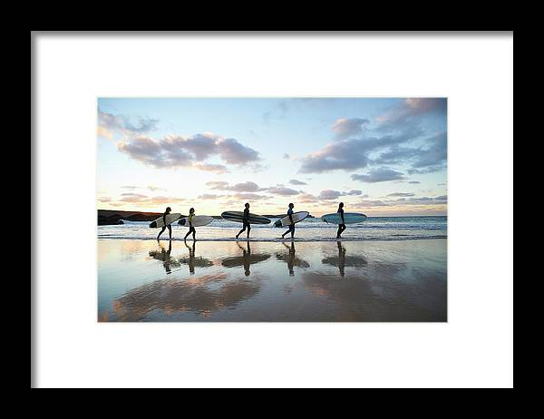 Young Men Framed Print featuring the photograph Five Surfers Walk Along Beach With Surf by Dougal Waters