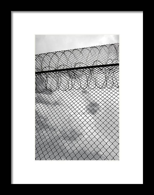 Prison Framed Print featuring the photograph Forbidding Prison Fence by John Orsbun
