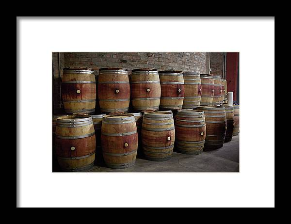 Stellenbosch Framed Print featuring the photograph French Wine Barrels Stacked At Winery by Klaus Vedfelt