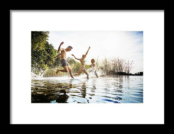 Young Men Framed Print featuring the photograph Friends Splashing In Water At Lake Together by TommL