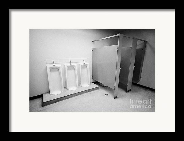 Toilet Framed Print featuring the photograph full length urinals and cubicles in mens toilet of High school canada north america by Joe Fox