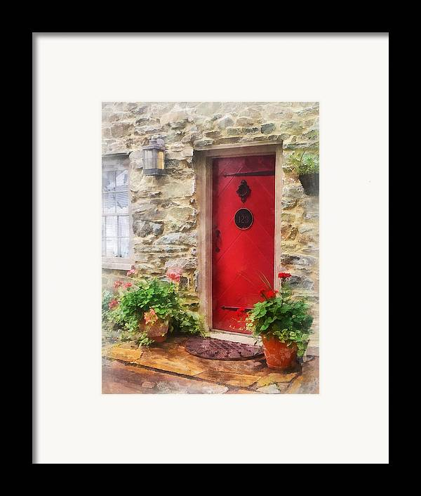 Door Framed Print featuring the photograph Geraniums By Red Door by Susan Savad