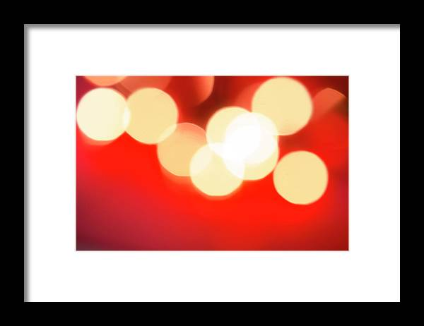 Christmas Lights Framed Print featuring the photograph Glowing Light On Red Background, Studio by Tetra Images