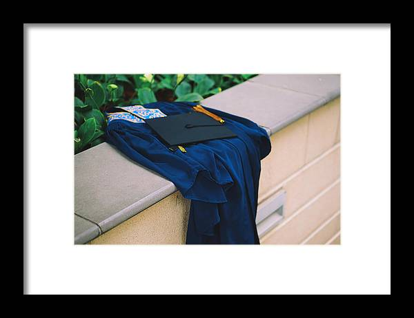 Education Framed Print featuring the photograph Graduation Gown With Mortarboard On Retaining Wall by Danial Najmi / EyeEm