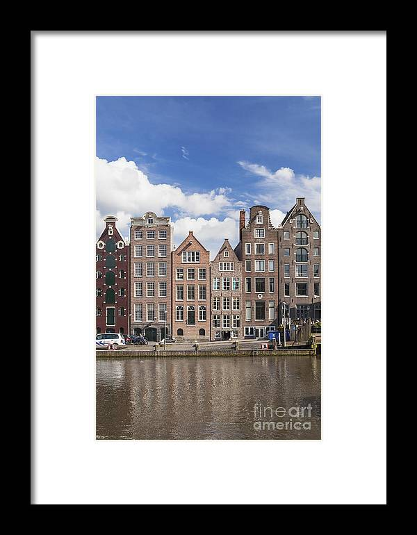 Amsterdam Framed Print featuring the photograph Historic Buildings Along The Damrak Canal In Amsterdam by Roberto Morgenthaler