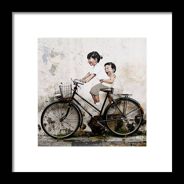 Little Children On A Bicycle Framed Print featuring the photograph Little Children on a Bicycle by Donald Chen