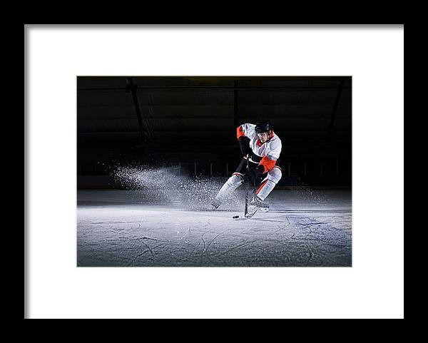 Focus Framed Print featuring the photograph Male Ice Hockey Player Taking Puck by Mike Harrington