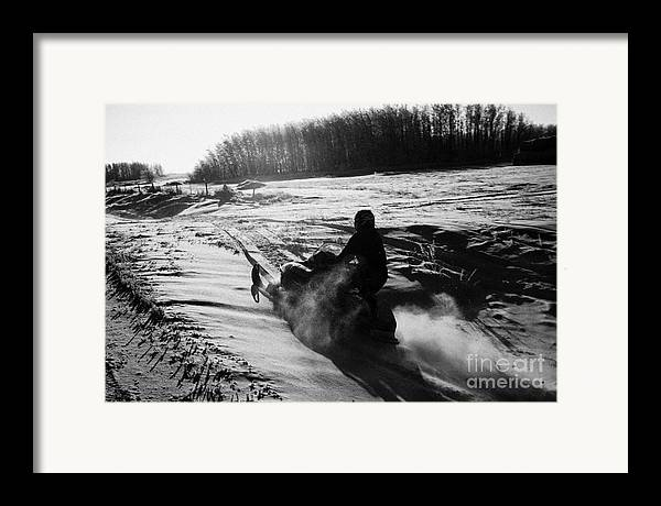 Man Framed Print featuring the photograph man on snowmobile crossing frozen fields in rural Forget canada by Joe Fox