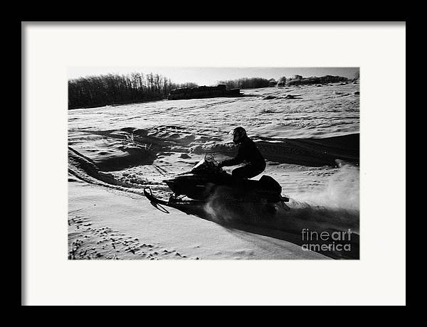 Man Framed Print featuring the photograph man on snowmobile crossing frozen fields in rural Forget Saskatchewan by Joe Fox