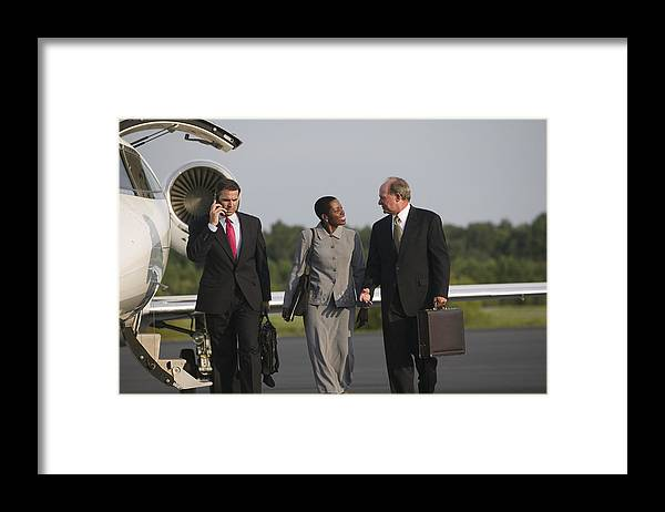 Three Quarter Length Framed Print featuring the photograph Men and woman talking near airplane by Comstock Images