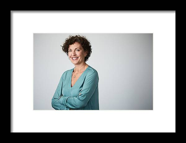 Expertise Framed Print featuring the photograph Mid adult businesswoman headshot on grey background. by Tempura
