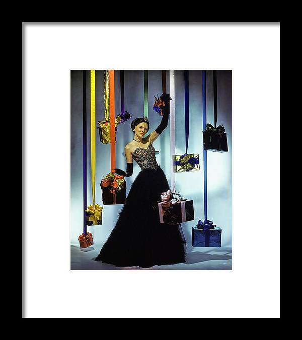Accessories Framed Print featuring the photograph Model Wearing An Evening Gown Among Gifts by John Rawlings