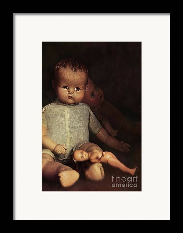 Atmosphere Framed Print featuring the photograph Old Dolls Sitting On Wooden Table by Sandra Cunningham