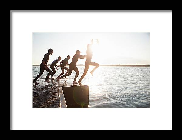 Adolescence Framed Print featuring the photograph Pier Jumping by Solstock