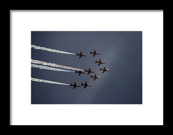 Accuracy Accurate Aerial Aerobatic Aeronautic Agile Agility Air Aircraft Arrows Blue Display Excitement Expertise Flier Flying Force Formation Hawk High Jet Motivation Pattern Pilots Plane Power Precise Precision Professionals Raf Red Royal Skill Sky Speed Stunt Team Teamwork White Framed Print featuring the photograph Red Arrows Flying Into The Sun by Steve Ball