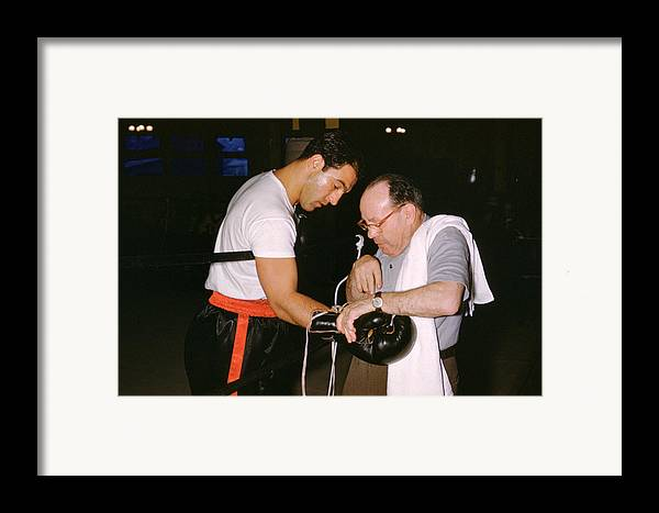 Marvin Newman Framed Print featuring the photograph Rocky Marciano Looking At Glove by Retro Images Archive