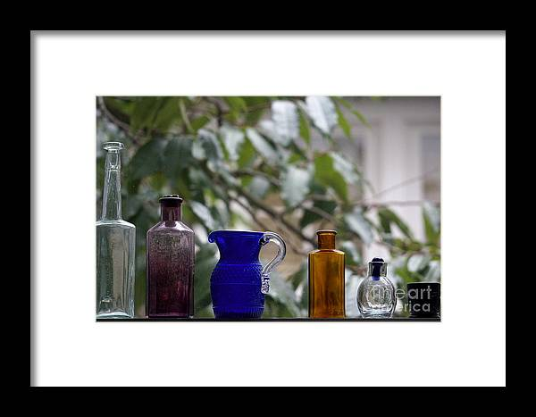 Glass Framed Print featuring the photograph Row Of Colorful Glass Bottles by John Mitchell