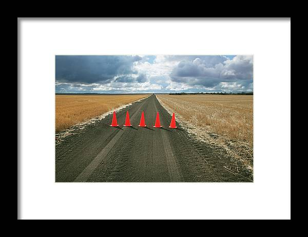 Orange Color Framed Print featuring the photograph Safety Cones Lined Up Across A Rural by Benjamin Rondel / Design Pics