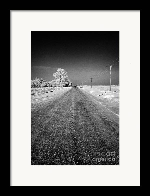 Salt Framed Print featuring the photograph salt and grit covered rural small road in Forget Saskatchewan Canada by Joe Fox