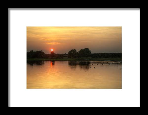 Landscape Framed Print featuring the photograph Setting Sun Glows Through Trees And Reflected In Still Lake Wate by Matthew Gibson