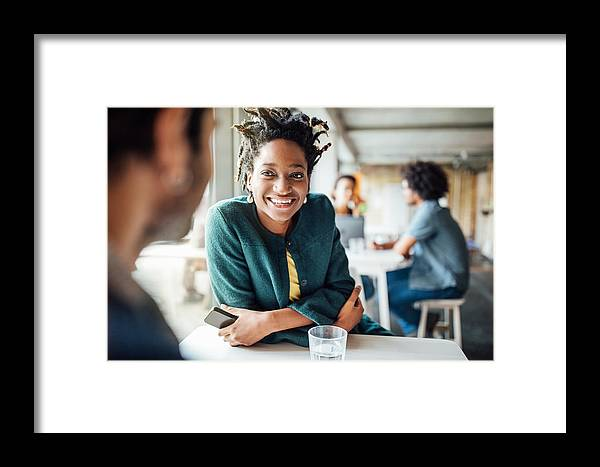 New Business Framed Print featuring the photograph Smiling Businesswoman Sitting With Colleague In Cafeteria by Luis Alvarez