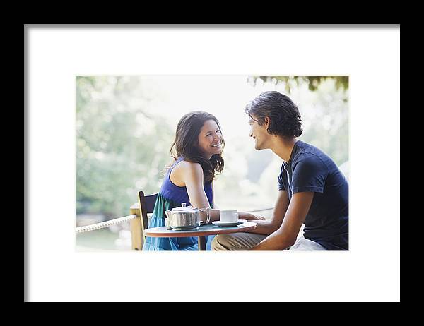 Young Men Framed Print featuring the photograph Smiling couple having tea outdoors by Tom Merton