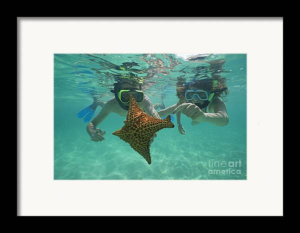 People Framed Print featuring the photograph Snorkellers Holding A Four Legs Starfish by Sami Sarkis