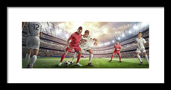 Soccer Uniform Framed Print featuring the photograph Soccer Player Tackling Ball In Stadium by Dmytro Aksonov