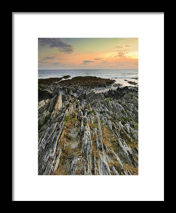 Sunset Framed Print featuring the photograph Stunning Vibrant Rock Formation Against Ocean And Beautiful Suns by Matthew Gibson