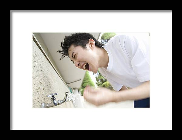 Education Framed Print featuring the photograph Teenage boy in gym cloth washing face and yelling, blurred motion by Daj