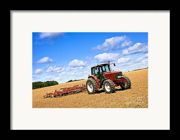 Tractor Framed Print featuring the photograph Tractor In Plowed Farm Field by Elena Elisseeva
