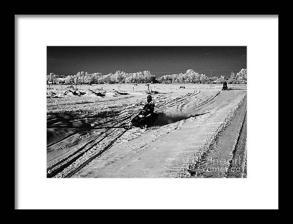 Man Framed Print featuring the photograph two men on snowmobiles crossing frozen fields in rural Forget Saskatchewan Canada by Joe Fox