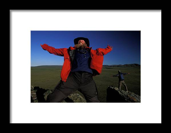 Arms Outstretched Framed Print featuring the photograph Two People Stand On The Edge Of A Cliff by Peter McBride