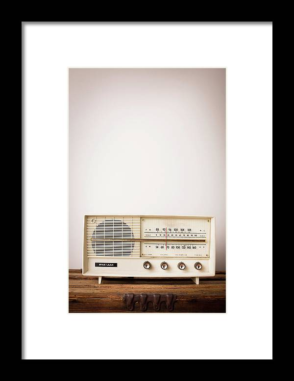 Desaturated Framed Print featuring the photograph Vintage Beige Radio Sitting On Wood by Ideabug