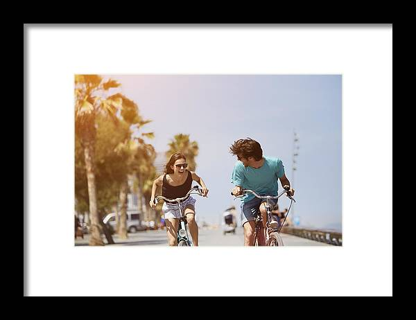 Young Men Framed Print featuring the photograph Woman chasing man while riding bicycle by Morsa Images