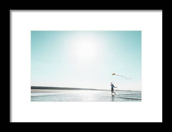 Three Quarter Length Framed Print featuring the photograph Woman Flying Kite On Beach by Dan Brownsword
