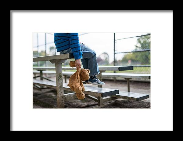 Empty Framed Print featuring the photograph Young boy sitting by himself on on bleachers. by FatCamera