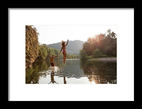 Young Men Framed Print featuring the photograph Young Couple Jumping Into River by Zave Smith