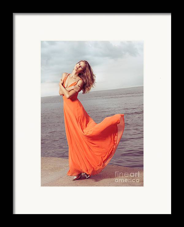 Woman Framed Print featuring the photograph Young Woman In Orange Dress Flying In The Wind At Sea Shore by Oleksiy Maksymenko