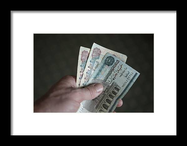 Egypt Framed Print featuring the photograph A Hand Holds Egyptian Pounds In Cash by Taylor S. Kennedy