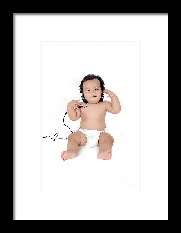 Baby Framed Print featuring the photograph A Chubby Little Girl Listen To Music With Headphones by Antoni Halim