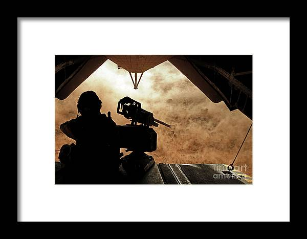 Dust Framed Print featuring the photograph A Marine Waits For Dust To Clear While by Stocktrek Images