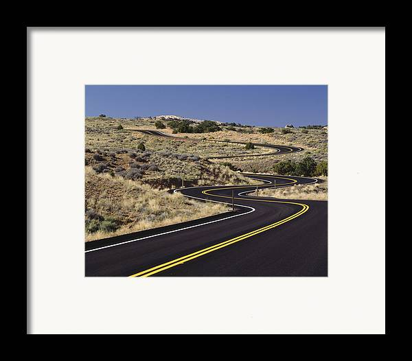 No People Framed Print featuring the photograph A Newly Paved Winding Road Up A Slight by Greg Probst
