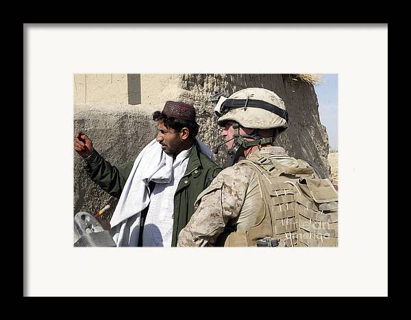 Marines Framed Print featuring the photograph A Soldier Talks To A Local Villager by Stocktrek Images